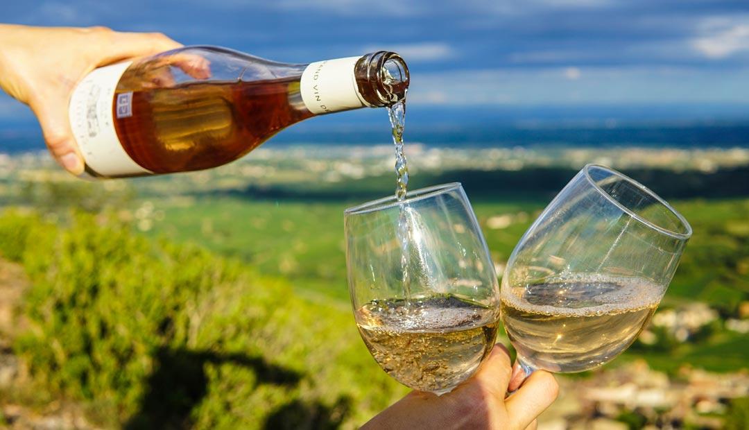Eine Weinschorle kann man einfach selber machen. Es können Weiß-, Rosé und Rotweine verwendet werden. (Foto: Elle Hughes / Unsplash)